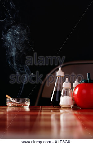 Smoking cigarette in ashtray on table with condiments - Stock Photo