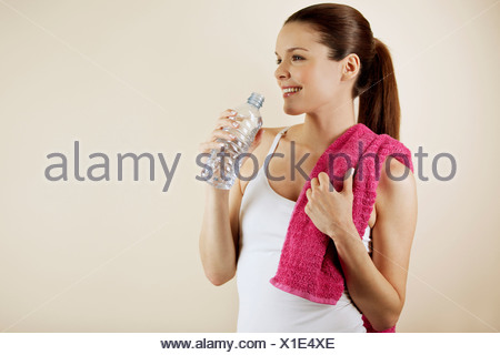 A young woman wearing fitness clothing, drinking a bottle of water - Stock Photo