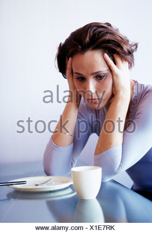 Woman leaning on the table feeling miserable - Stock Photo