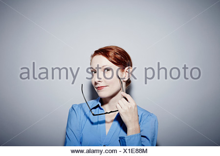 Studio portrait of young woman holding spectacles - Stock Photo