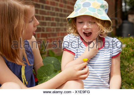 Two sisters in garden with buttercup flower - Stock Photo