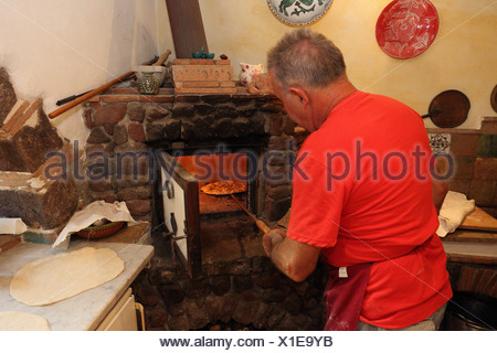 Torre Alfina, Italy, pizza baker pushes a pizza in a stone oven - Stock Photo