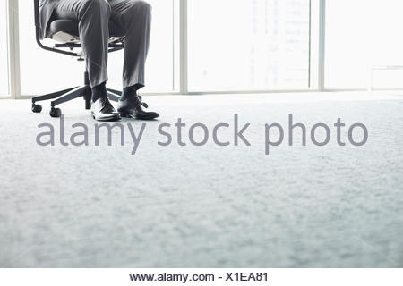 Low section of businessman sitting on office chair - Stock Photo