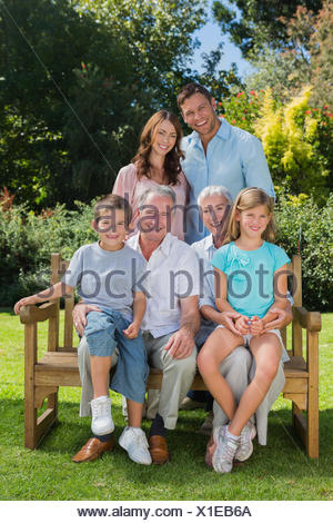 Smiling multi generation family sitting on a bench in park - Stock Photo