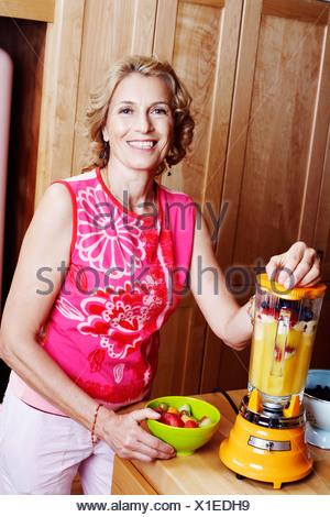 Portrait of a mature woman preparing mango shake in the kitchen - Stock Photo