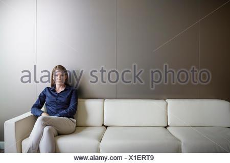 Portrait confident businesswoman with legs crossed on sofa - Stock Photo