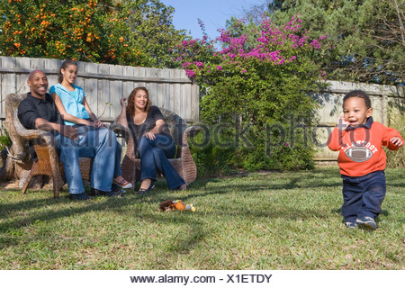 Happy African American family sitting in yard outdoors - Stock Photo
