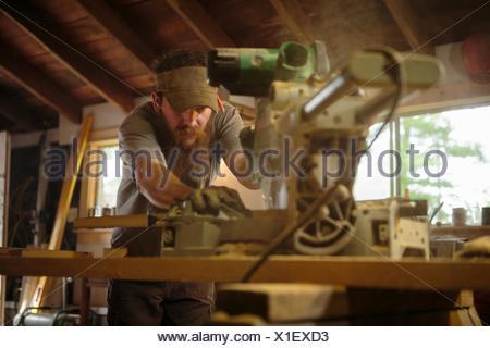 Wood artist using machinery in workshop