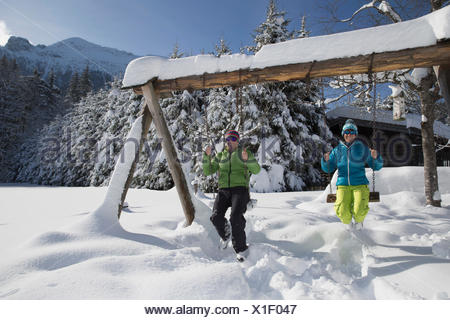 Germany, Bavaria, Inzell, couple sitting on swings in snow-covered landscape - Stock Photo