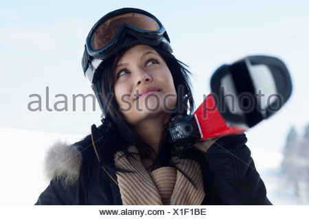 Young female wearing ski goggles and carrying skis - Stock Photo