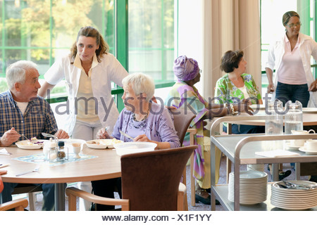 A group of senior people having lunch together in a retirement home - Stock Photo