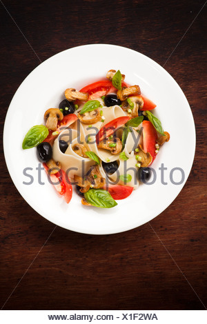 Pasta pappardelle with mushrooms, tomatoes, olives and basil leaves - Stock Photo