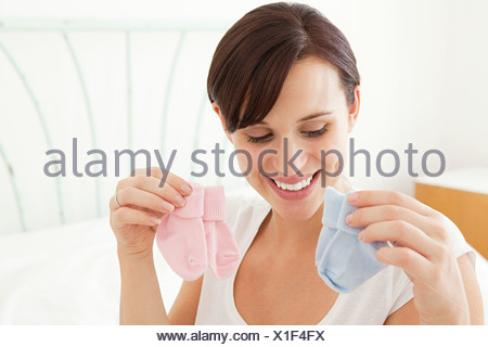 Pregnant woman looking at blue and pink baby socks - Stock Photo