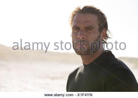 Close up portrait serious sportsman at beach - Stock Photo