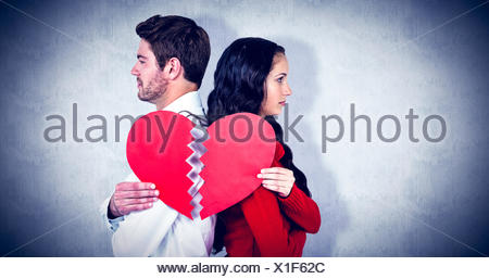 Composite image of couple back to back holding heart halves - Stock Photo