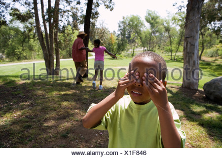 Senior man playing hide and seek with grandchildren 6 10 in park boy covering eyes in foreground - Stock Photo