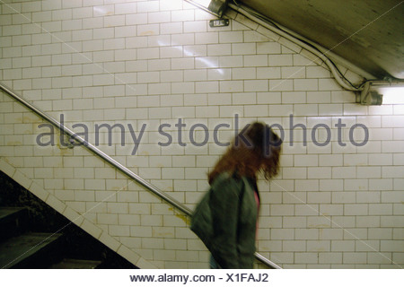 Young woman walking down stairs - Stock Photo