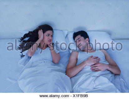 Woman covering her ears while man snores - Stock Photo