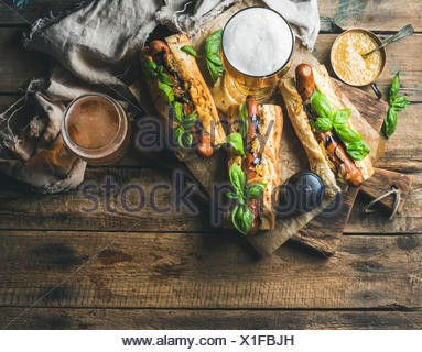 Glasses of wheat unfiltered beer and homemade grilled sausage dogs in baguette with mustard, caramelised onion and herbs on serv - Stock Photo