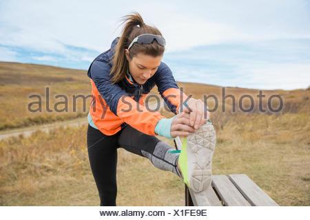 Runner stretching leg on rural bench - Stock Photo