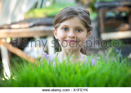 On the farm. A girl standing smiling by a glasshouse bench looking over the green shoots of seedlings growing in trays. - Stock Photo