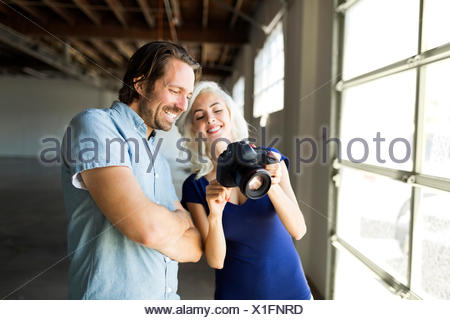 Woman and man looking at pictures in digital camera - Stock Photo
