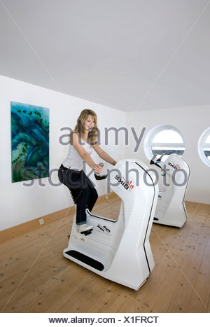 Young woman working out on a stationary bicycle - Stock Photo