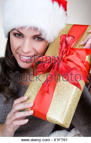 A young woman wearing a Santa hat, holding a Christmas present - Stock Photo
