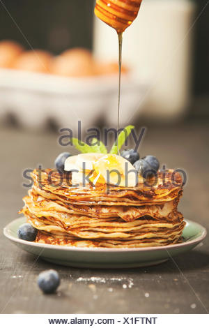 Pancake tower with fresh bananas, blueberries and honey on a rustic table - Stock Photo