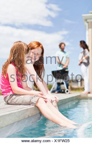 Girls dangling feet in swimming pool Stock Photo