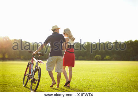 Couple pushing cycle whilst strolling in park - Stock Photo