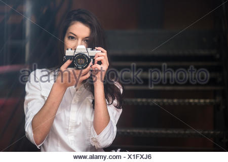Young woman taking photograph with SLR camera - Stock Photo