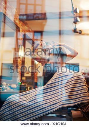 View through window of hairdresser cutting customer's hair - Stock Photo