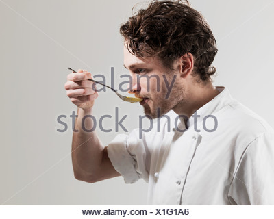 Chef tasting food from spoon against white background - Stock Photo