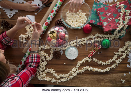 Mother and children stringing Christmas popcorn decoration - Stock Photo