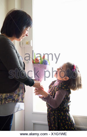 Young girl giving mother flowers - Stock Photo