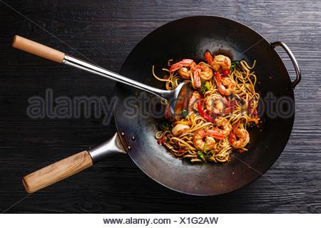 Udon stir-fry noodles with shrimp and vegetables in wok pan on black burned wooden background - Stock Photo
