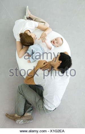 Parents and baby relaxing on ottoman, baby holding mother's hand, overhead view - Stock Photo