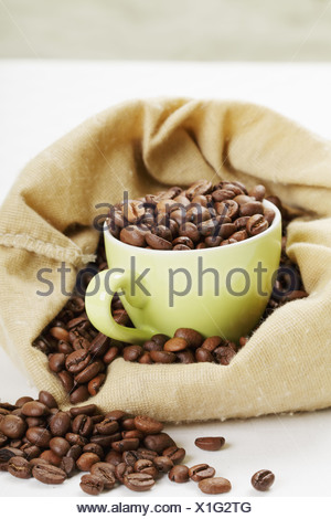 Green cup filled with coffee beans in bag - Stock Photo