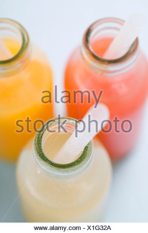 Three fruit juices in bottles with straws (overhead view) - - Stock Photo