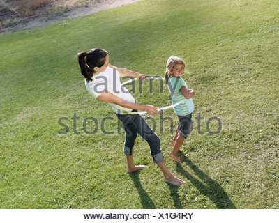 Mother and daughter 6 8 playing with hula hoop on grass in park smiling side view elevated view - Stock Photo