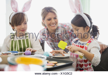 Mother with children decorating Easter cookies - Stock Photo