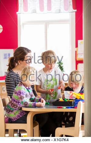 Sweden, Children playing with teacher in kindergarten - Stock Photo