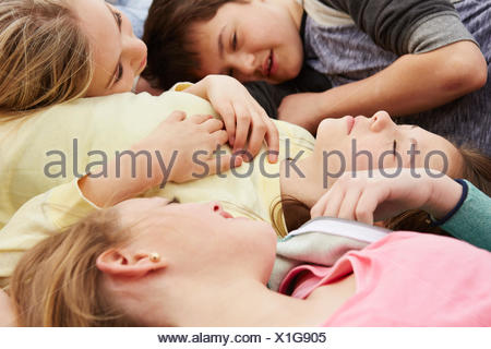 Five boys and girls lying down with eyes closed - Stock Photo
