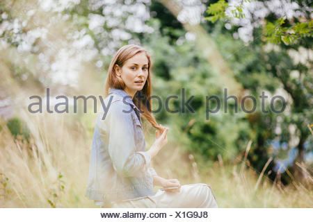 Portrait of young woman with hand in hair in field - Stock Photo