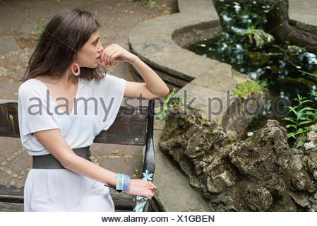 Young woman sitting on bench near pond - Stock Photo