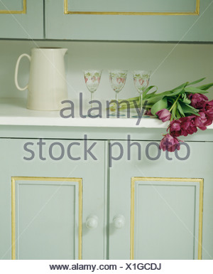 Close-up of red tulips beside white jug and wine-glasses on white worktop above pale turquoise cupboard - Stock Photo