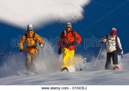 three persons on snow shoes, walking in deep powder snow, France, Alps - Stock Photo