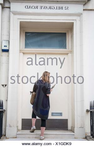 A young long hair dark blond caucasian woman in her 20´s, 30´s with her feet lifted on the stair of a huge door on Belgrade road in London, England - Stock Photo