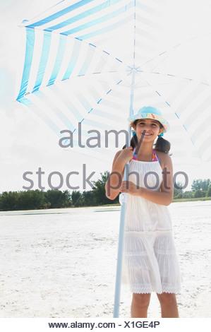 Girl holding umbrella on beach - Stock Photo